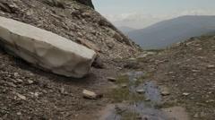 Block of snow melting on mountain with water flowing down hill - stock footage