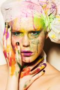 Close-up portrait of young woman with unusual makeup. Model posing with paint - stock photo