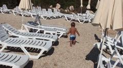 Toddler walks away between empty sun beds Stock Footage