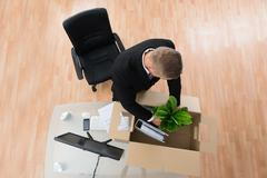 Stock Photo of Businessman Packing Belongings In Cardboard Box At The Desk