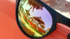 The reflection of a beach umbrella in sunglasses Stock Footage
