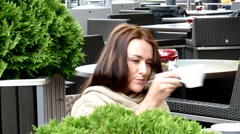 Stock Video Footage of Pretty young woman drinking coffee in a cozy cafe