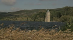 Lake with water ripples and wheat fields being blown by the wind, church ruins Stock Footage