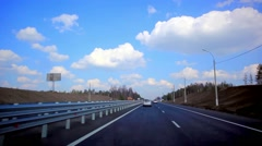 Cars drives on the asphalt road and sky background with clouds - stock footage