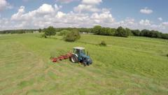 Drone fast low flight over farmer in tractor mowing a green fresh grass field 4k Stock Footage