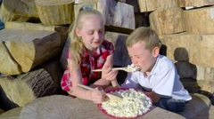 Stock Video Footage of Children eat natural cottage cheese with wooden spoons and laughing