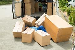Unconscious Male Worker Lying On Street Surrounded With Boxes - stock photo