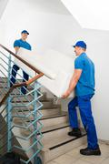 Two Happy Male Movers In Uniform Carrying White Sofa On Staircase - stock photo