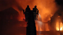 Firefighters spray water from ladder truck onto fire Stock Footage