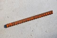 Cut piece of corroded stained rusty metal armature fitting on bubbled concret Stock Photos