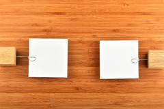 Two paper notes with holders in different directions on wood - stock photo