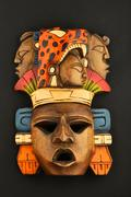 Indian Mayan Aztec wooden carved painted mask isolated on black Stock Photos