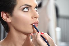Beautiful model having lip liner applied by makeup artist Stock Photos