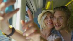Attractive couple in love take a photo of themselves on a train in slow motion Stock Footage