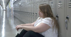 Teenage female sitting on floor of high school hallway upset 4k Stock Footage