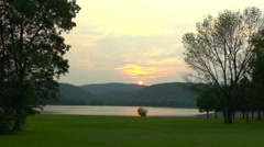 The Sun Sets Behind the Mountains and Lake Stock Footage