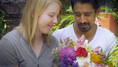 A Latin man brings a woman flowers outside in natural lighting Stock Footage