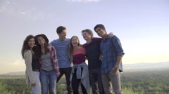 Group Of Teens Hold Each Other And Smile, Then Jump In The Air (Slow Motion) - stock footage