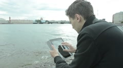 Man using tablet pc at the lake - stock footage