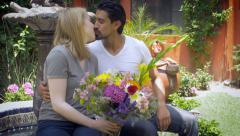 An attractive hispanic man brings flowers to a young blond woman wide shot Stock Footage