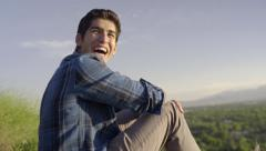 Young Man Sits, Looks Out At View Of Valley, He Turns And Laughs (Slow Motion) Stock Footage