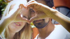 An attractive couple in love smile and make a heart with their hands Stock Footage