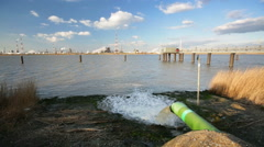 Wastewater Pipe And Refinery At River Stock Footage