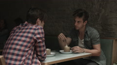 Men sitting and talking in cafe Stock Footage