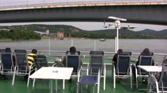 Passengers sitting on the top deck of a cruise boat passing under a bridge Stock Footage