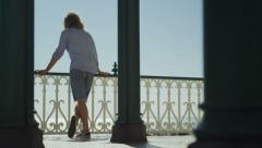 Attractive single man looking out to sea from a balcony in slow motion Stock Footage