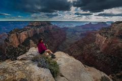 Hiker looking down Cape Royal Overlook Grand Canyon North Rim Wotans Throne - stock photo