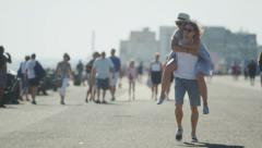 Young couple having fun as the male piggy backs his girlfriend in slow motion - stock footage