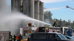 Firefighters spraying water on fire at an industrial complex Stock Footage
