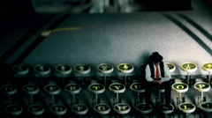 tiny 40s film nior writer sitting on a vintage typewriter - stock footage