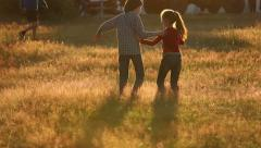 Boy with a girl playing in a field at sunset Stock Footage
