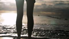 Young woman in shorts standing alone on the beach in the sunset. Stock Footage