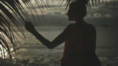 Silhouette of young woman looking at the sunset. Rear view. - stock footage