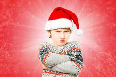 Portrait of a boy in christmas hat with angry and unhappy gesture - stock photo
