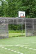 Soccer goal and basketball hoop on outdoor playground with synthetic field Stock Photos