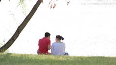 man and woman sitting on the bank of the river near a tree, talking - stock footage