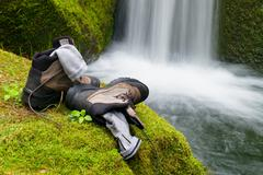 Hiker high boots and sweaty grey socks. Resting on the boulder at the  nice m Stock Photos