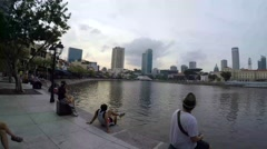 4k UHD video of people relaxing on the bank of  Singapore River Stock Footage