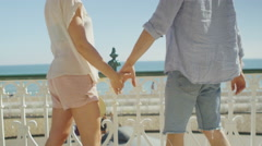 Young couple holding hands embrace and look out to sea on a nice sunny day - stock footage