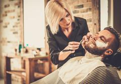 Client during beard shaving in barber shop Stock Photos