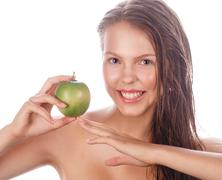 Teen girl with nude makeup holding green apple. - stock photo
