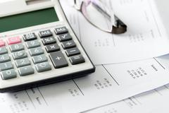 Financial statement with calculator and glasses Stock Photos