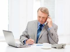 Busy older businessman with laptop and telephone Stock Photos
