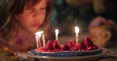 5 year old girl child blowing birthday candles on strawberry cake. 4K UHD. Stock Footage