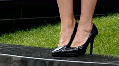 Close-up of young woman's legs in high-heeled black shoes Stock Footage