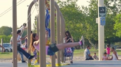 Happy diverse group children swinging playing swings park playground Slow motion Stock Footage